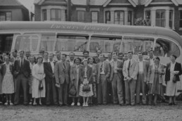 Photo of a large group of people in front of a coach