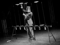 Vintage photo of a man with a bucket on his head, spinning plates