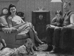 Vintage photo of a smiling family in their living room with a radio