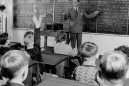 Vintage photo of a male teacher at a blackboard teaching children