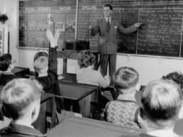Vintage photo of a male teacher at a blackboard teaching children
