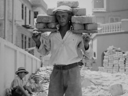 Vintage photo of a man carrying bricks in a street
