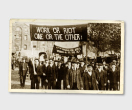 "Vintage photo of a group of people and a policeman on a march with a banner reading ""Work or riot, one or the other"""
