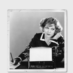 Vintage photo of a woman on the phone, writing a note and sitting in front of a typewriter