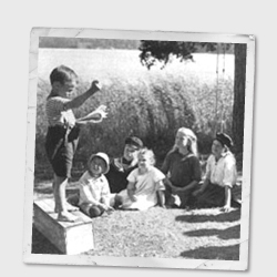 Vintage photo of a boy standing on a box addressing a group of children